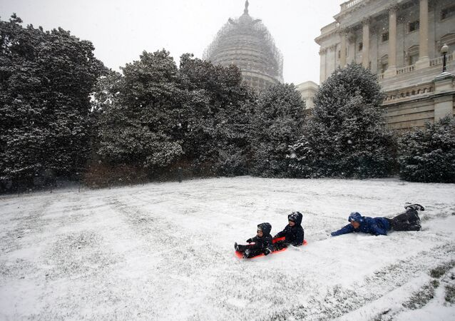 Ben Cichy slips as he pushes his sons Adrian, 18 months, and Logan 3, as they sled in the snow on Capitol Hill.