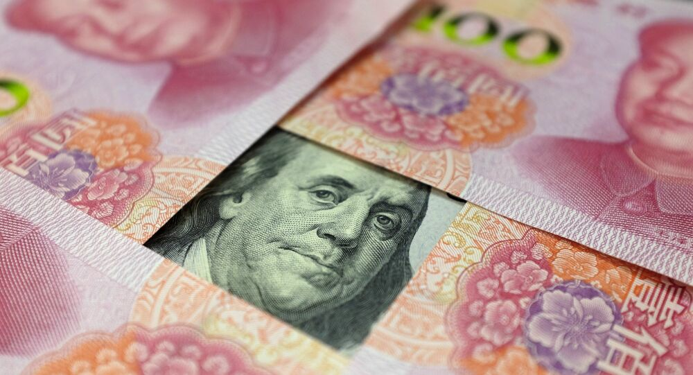A US 100-dollar banknote with a portrait of Benjamin Franklin and Chinese 100-yuan banknotes with portraits of late Chinese Chairman Mao Zedong are seen in the picture illustration in Beijing, China
