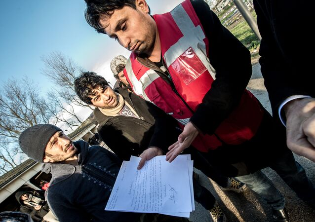 A translator shows documents to Afghan migrants during a roam by members of The French Office for the Protection of Refugees and Stateless Persons (OFPRA), at the Jules Ferry reception centre near the Jungle migrant camp in Calais, on January 14, 2016.