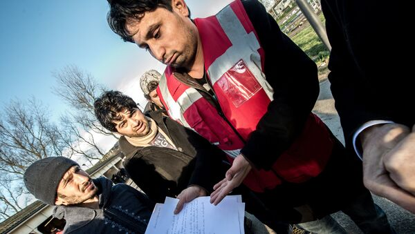A translator shows documents to Afghan migrants during a roam by members of The French Office for the Protection of Refugees and Stateless Persons (OFPRA), at the Jules Ferry reception centre near the Jungle migrant camp in Calais, on January 14, 2016. - Sputnik International