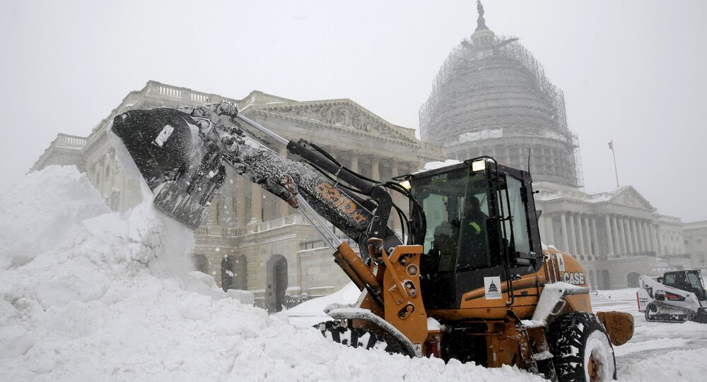A Capitol Hill employee uses a heavy earth moving machine to clear snow during a winter storm in Washington January 23, 2016. A winter storm dumped nearly 2 feet (58 cm) of snow on the suburbs of Washington, D.C., on Saturday before moving on to Philadelphia and New York, paralyzing road, rail and airline travel along the U.S. East Coas