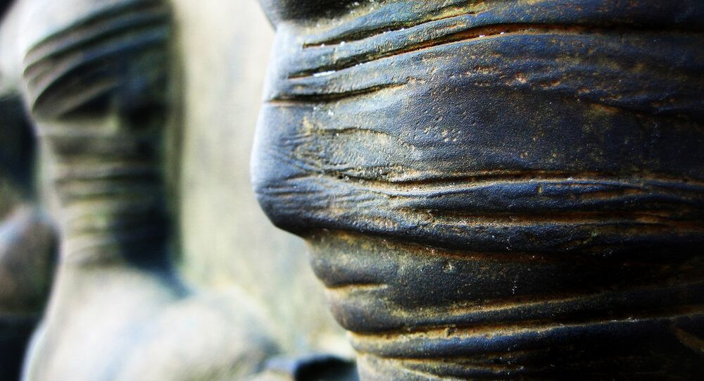 Faces around the plinth of a statue
