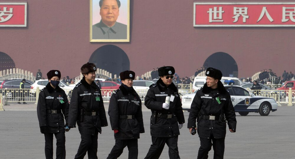 Chinese police officers march across Tiananmen Square outside the Great Hall of the People during a hazy day in Beijing, China, Sunday, March 9, 2014