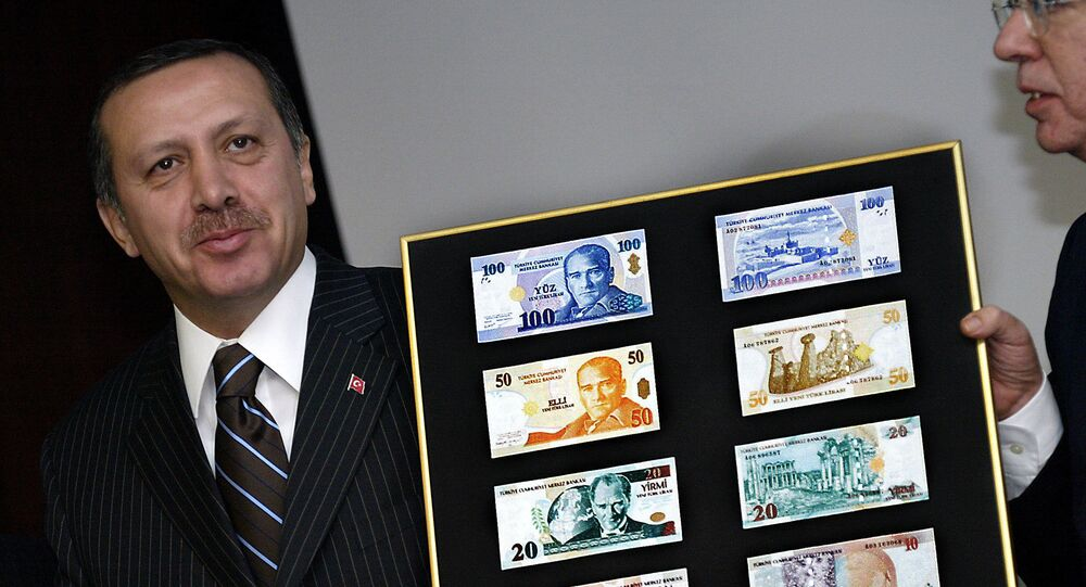 Turkish Prime Minister Recep Tayyip Erdogan holds a board featuring the new Turkish lira samples (File)