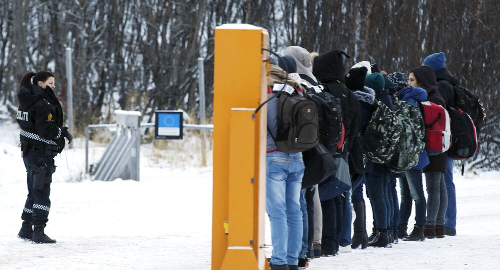 Migrants receive instructions from a Norwegian police officer at Storskog boarder crossing station near Kirkenes, after crossing the boarder between Norway and Russia on November 16, 2015