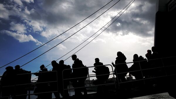 Refugees and migrants are silhouetted as they arrive aboard the passenger ferry Ariadne at the port of Piraeus, near Athens, Greece, January 4, 2016. - Sputnik International