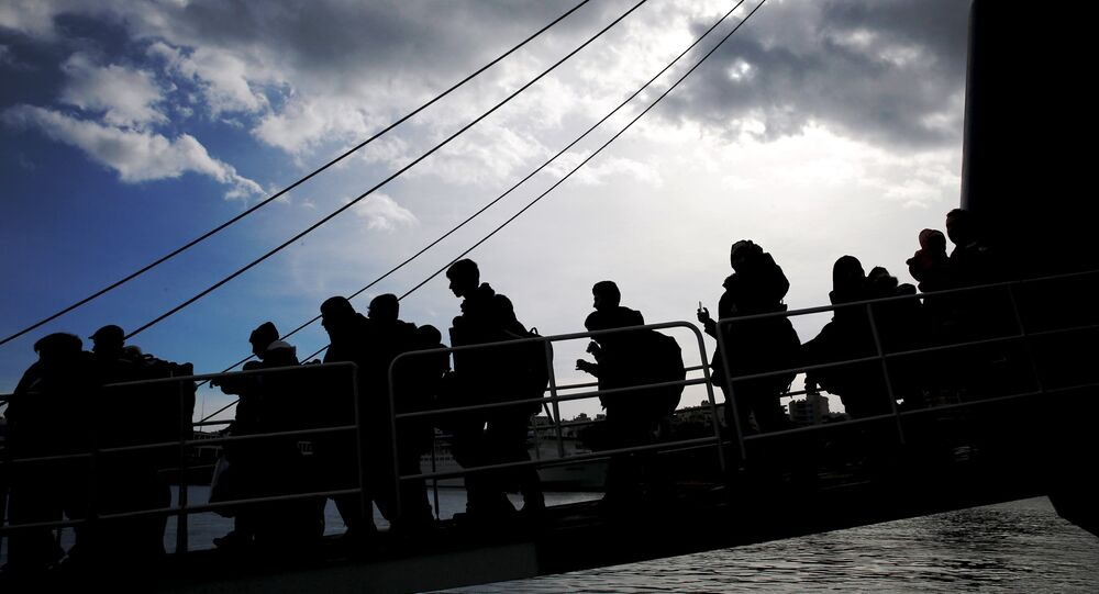 Refugees and migrants are silhouetted as they arrive aboard the passenger ferry Ariadne at the port of Piraeus, near Athens, Greece, January 4, 2016.