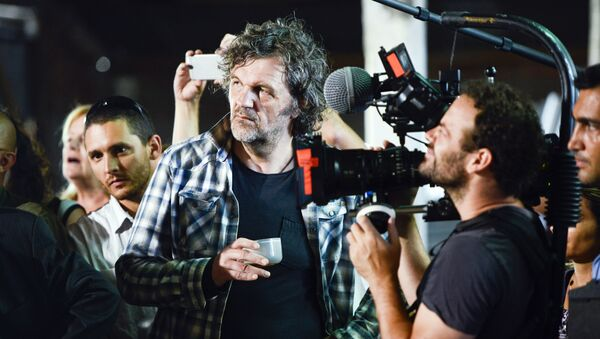 Serbian filmmaker Emir Kusturica, center, stands next to a cameraman while documenting the inauguration of an agricultural trade school that borders the family farm of former President Jose Mujica, on the outskirts of Montevideo, Uruguay, Thursday, March 5, 2015 - Sputnik International