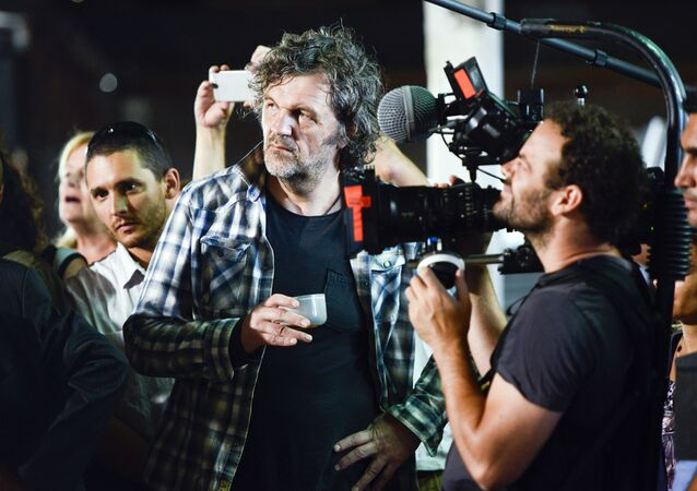 Serbian filmmaker Emir Kusturica, center, stands next to a cameraman while documenting the inauguration of an agricultural trade school that borders the family farm of former President Jose Mujica, on the outskirts of Montevideo, Uruguay, Thursday, March 5, 2015