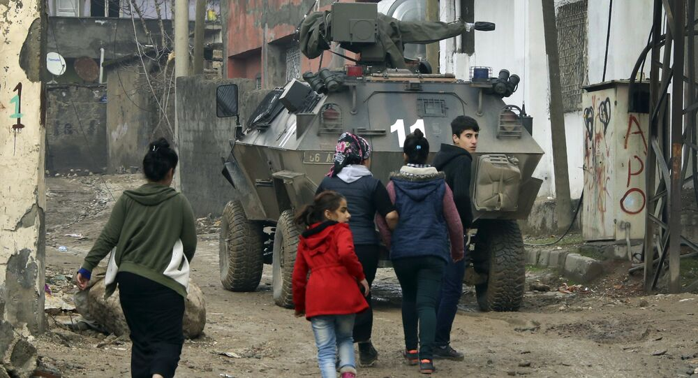 Backdropped by a Turkish forces armoured personnel carrier, residents walk around after the 24-hour curfew was lifted, in the mostly-Kurdish town of Silopi, in southeastern Turkey, near the border with Iraq, Tuesday, Jan. 19, 2016