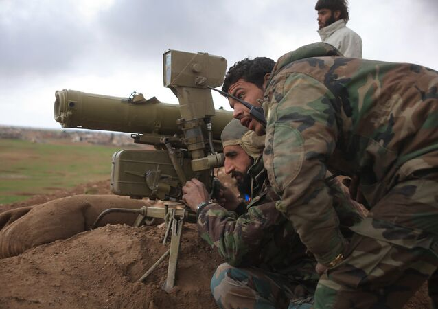 Syrian pro-government forces adjust a man-portable anti-tank system as they hold a position during a military operation against Daesh militants