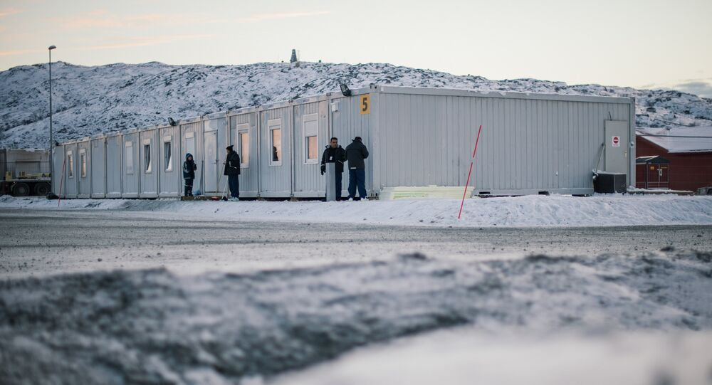 Refugees stand in front of residential containers at the arrival centre for refugees near the town on Kirkenes