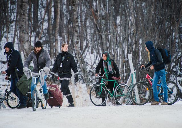 Refugees walk alongside there bikes to the Norwegian border crossing station at Storskog after crossing the border from Russia on November 12, 2015 near Kirkenes