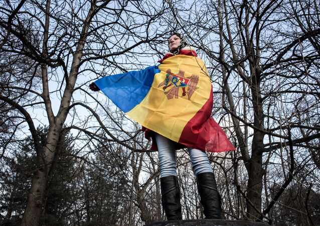 A participant in an opposition rally in Chisinau wrapped in Moldova's national banner