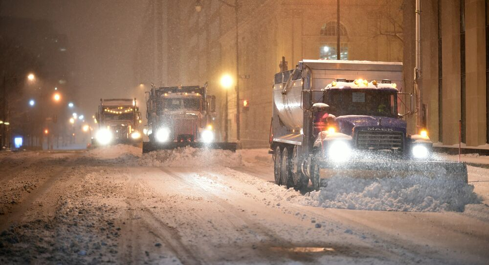Snow plows clean the snow from a street during a snowstorm in downtown Washington, DC on January 22, 2016