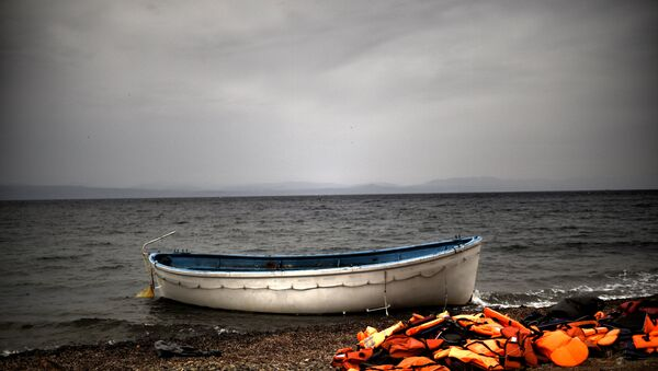 Life jackets and a boat that were used by refugees and migrants to cross the Aegean sea from Turkey lie abandoned on a beach on the Greek Island of Lesbos on October 8, 2015. - Sputnik International