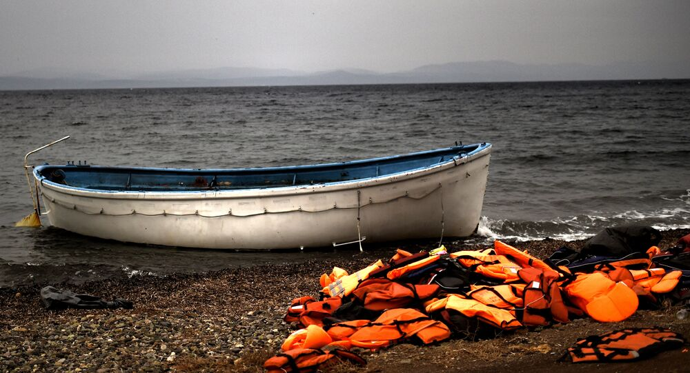 Life jackets and a boat that were used by refugees and migrants to cross the Aegean Sea from Turkey lie abandoned on a beach on the Greek Island of Lesbos on 8 October 2015.
