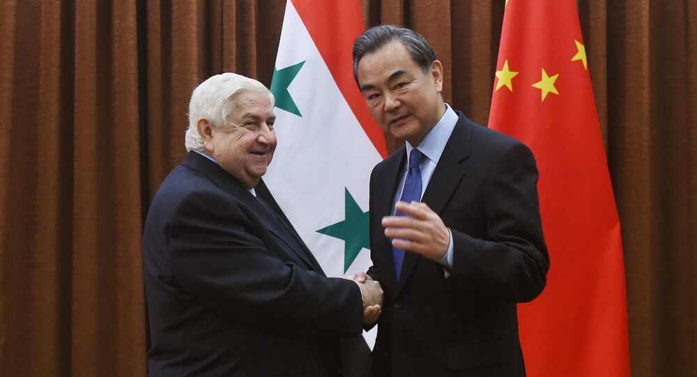 Syrian Foreign Minister Walid Muallem (L) is welcomed by Chinese Foreign Minister Wang Yi before a meeting in Beijing on December 24, 2015