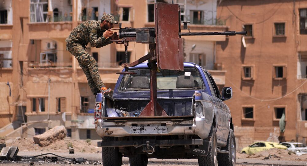 A member of the Kurdish People's Protection Units (YPG) mans a mounted machine gun in the Al-Nashwa neighbourhood in the northeastern Syrian province of Hasakeh on July 26, 2015
