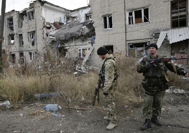Ukrainian servicemen walks in the yard of a destroyed building in the Pisky village near Donetsk on October 26, 2015