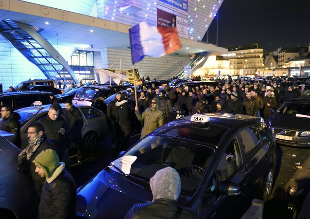Paris taxi drivers gather at the Porte Maillot during a nation-wide strike by France's 5,6 million-strong civil servants, on January 26, 2016 in Paris, to protest against labour reforms proposed last September affecting pay and career advancement