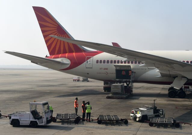 Airport workers load an Air India jet at the main terminal of the Indira Gandhi International airport in New Delhi on November 25, 2014