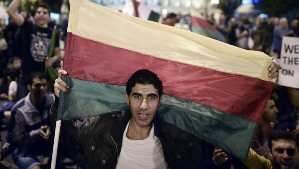 A man holds the flag of the Syrian Kurdish Democratic Union Party (PYD) as Kurds living in Greece protest in central Athens on October 8, 2014 - Sputnik International
