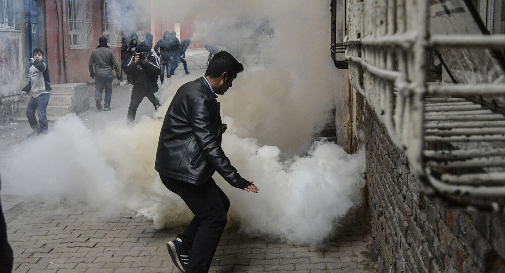 People react as tear gas is sprayed during clashes with Turkish police at the Sur district in Diyarbakir, on January 3, 2016