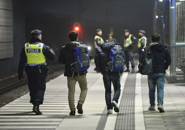 A police officer escorts migrants from a train at Hyllie station outside Malmo, Sweden. Picture taken November 19, 2015