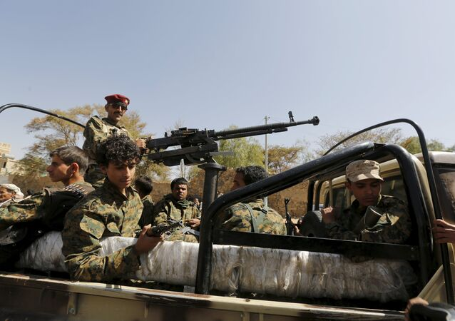Houthi militants ride on the back of a patrol truck (File)