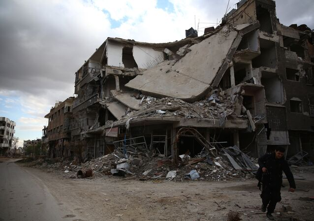 A photographer walks in the neighbourhood of Jobar, on the eastern outskirts of the capital Damascus, on January 23, 2016