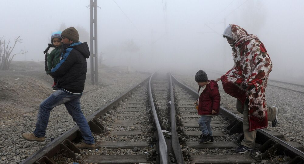 Migrants cross the railway tracks as they wait to cross the Greek-Macedonian border near the village of Idomeni, Greece, January 28, 2016