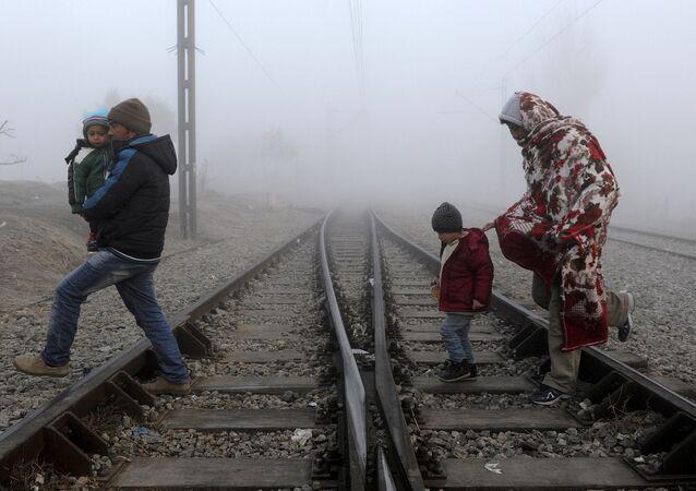Migrants cross the railway tracks as they wait to cross the Greek-Macedonian border near the village of Idomeni, Greece, January 28, 2016