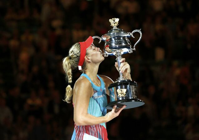 Germany's Angelique Kerber kisses the trophy after winning her final match against Serena Williams of the U.S. at the Australian Open tennis tournament at Melbourne Park, Australia, January 30, 2016