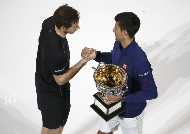 Serbia's Novak Djokovic (R) shakes hands with Britain's Andy Murray while holding the men's singles trophy after winning their final match at the Australian Open tennis tournament at Melbourne Park, Australia