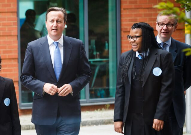 Britain's Prime Minister David Cameron (2-L) and Secretary of State for Education Michael Gove (R) walk with students during the opening of the Perry Beeches III Free School in Birmingham on September 3, 2013