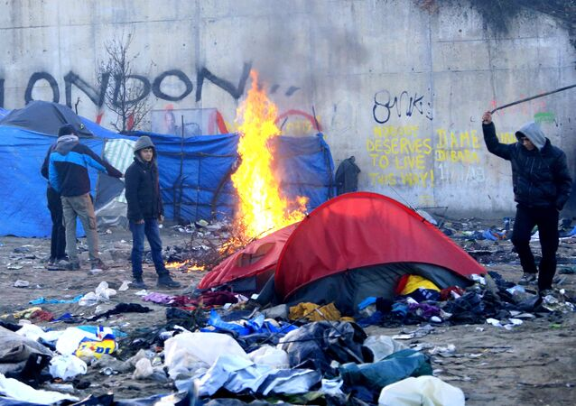 A migrant hits a former shelter with a stick in a dismantled area of the camp known as the Jungle, a squalid sprawling camp in Calais, northern France, January 17, 2016.