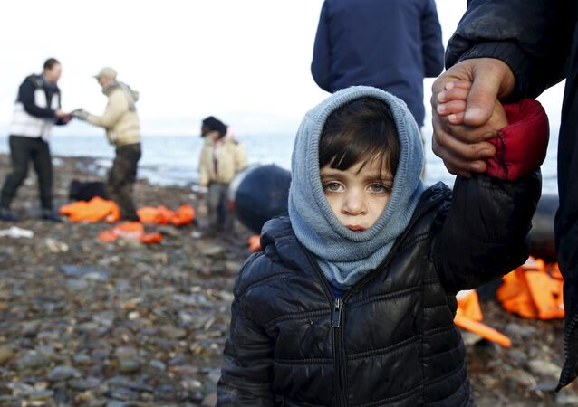 A Syrian refugee child looks on, moments after arriving on a raft with other Syrian refugees on a beach on the Greek island of Lesbos, January 4, 2016.