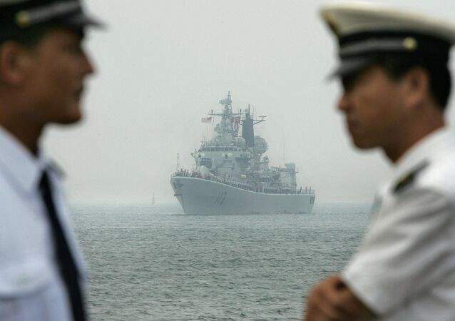 Chinese Navy officers wait dockside as a Chinese Navy warship escorting the arrival of the USS Curtis Wilbur (DDG54) (File)