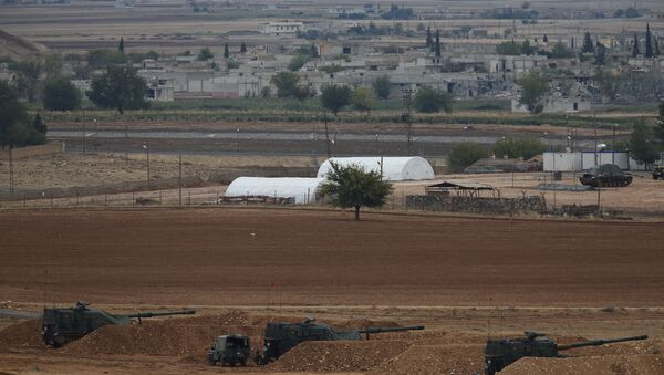 Men watch fighting across the border in Kobani from a hilltop on the outskirts of Suruc, Turkey, backdropped by Turkish army artillery positions near the Turkey-Syria border, Sunday, Oct. 26, 2014 - Sputnik International