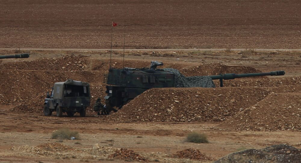 Turkish soldiers hold their positions with their artillery pieces, bottom, on a hilltop in the outskirts of Suruc, at the Turkey-Syria border, overlooking Kobani, Syria, background, during fighting between Syrian Kurds and the militants of Islamic State group, Thursday, Oct. 16, 2014