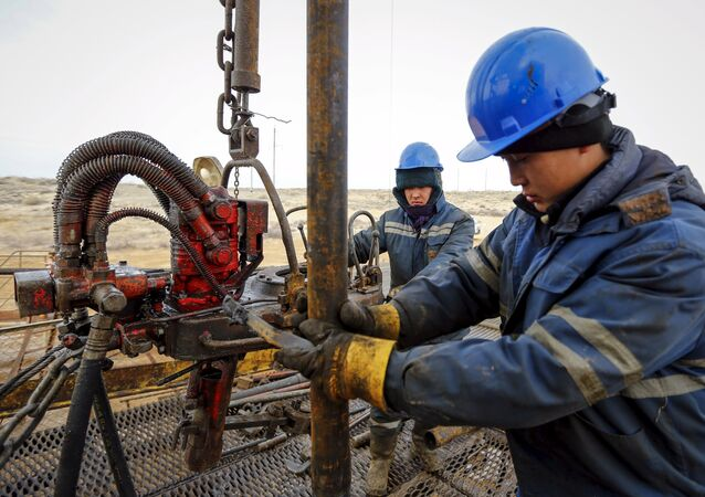 Workers carry out maintenance at an oil well on oil fields operated by a subsidiary of the KazMunayGas Exploration Production JSC in Kyzylorda region, southern Kazakhstan.