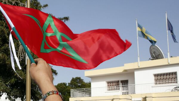 Moroccan woman waves her national flag outside the Swedish Embassy in Rabat, Morocco, as hundreds of protesters stage a protest against Sweden's diplomatic position on Moroccan-controlled Western Sahara, Sunday, Oct. 4, 2015 - Sputnik International