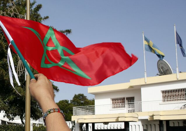 Moroccan woman waves her national flag outside the Swedish Embassy in Rabat, Morocco, as hundreds of protesters stage a protest against Sweden's diplomatic position on Moroccan-controlled Western Sahara, Sunday, Oct. 4, 2015