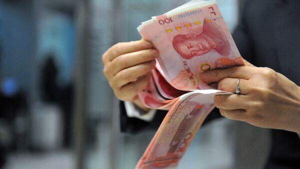 A bank employee counts 100-yuan banknotes at a bank in Hangzhou, east China's Zhejiang province on December 1, 2015. - Sputnik International