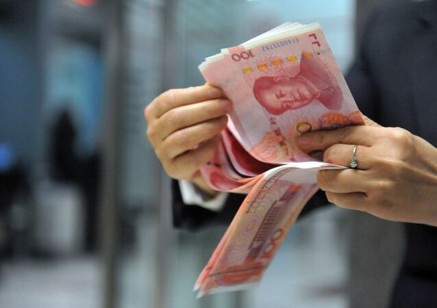 A bank employee counts 100-yuan banknotes at a bank in Hangzhou, east China's Zhejiang province on December 1, 2015.