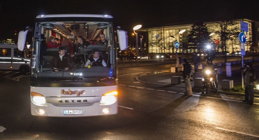 A bus carrying refugees with asylum status in Germany leaves the chancellery in Berlin on January 14, 2016, after it arrived from the Bavarian city of Landshut. . The bus carrying 31 refugees took them to a hotel where they will be able to spend the night before going to the destination of their choice