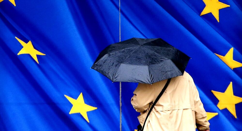 A woman carrying an umbrella walks towards the European Commission headquarters in Brussels, Belgium February 2, 2016.