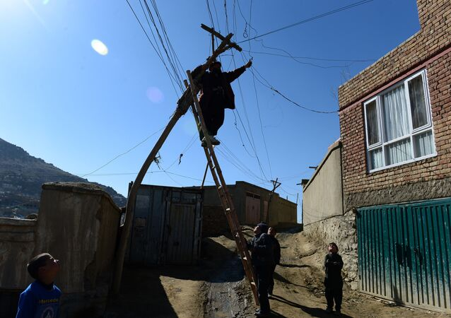 An Afghan electrician man repairs old power lines on a hillside in Kabul on March 1, 2014