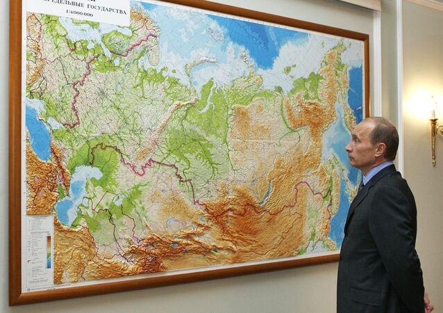 Russian President Vladimir Putin looks at a map in his country at his residence of Novo-Ogaryevo outside Moscow